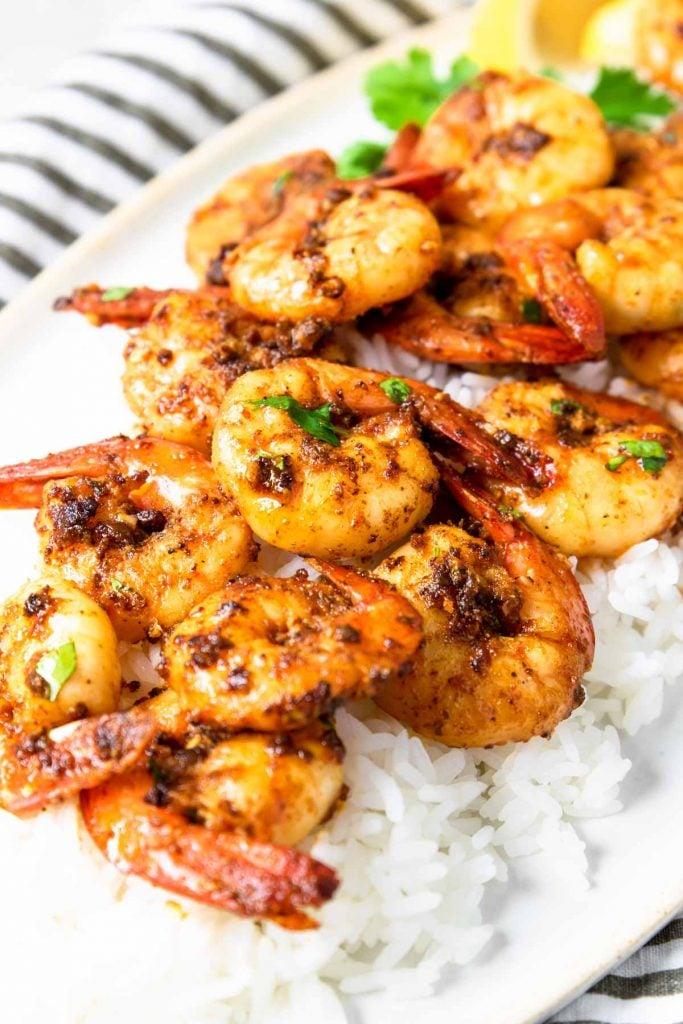cajun shrimp served over rice on a plate