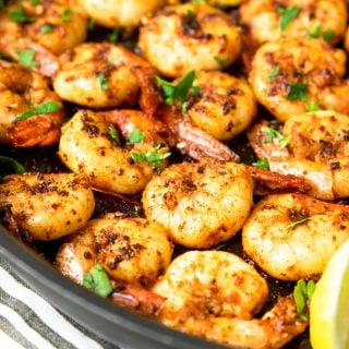 cajun shrimp cooked in a skillet with lemon wedges and parsley ganish