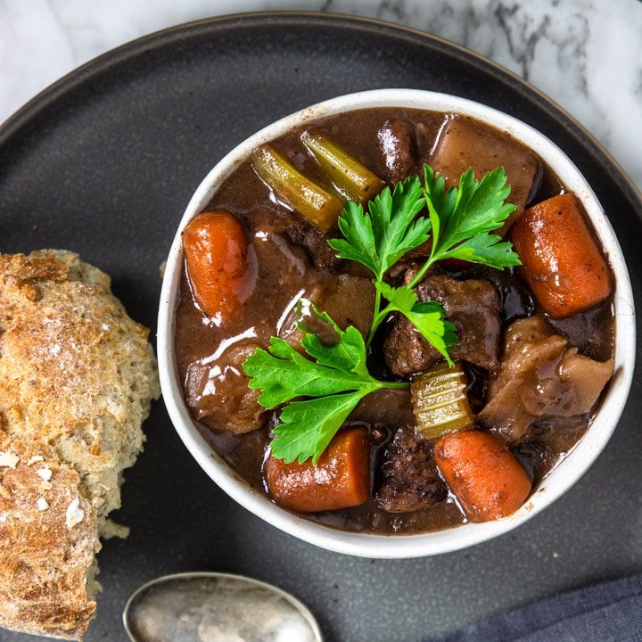 one bowl of red wine beef stew garnished with parsley