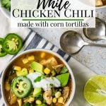 two bowls of white chicken chili topped with cilantro, avocado and jalapeno
