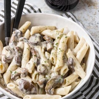 penne coated in a cream sauce with mushrooms.