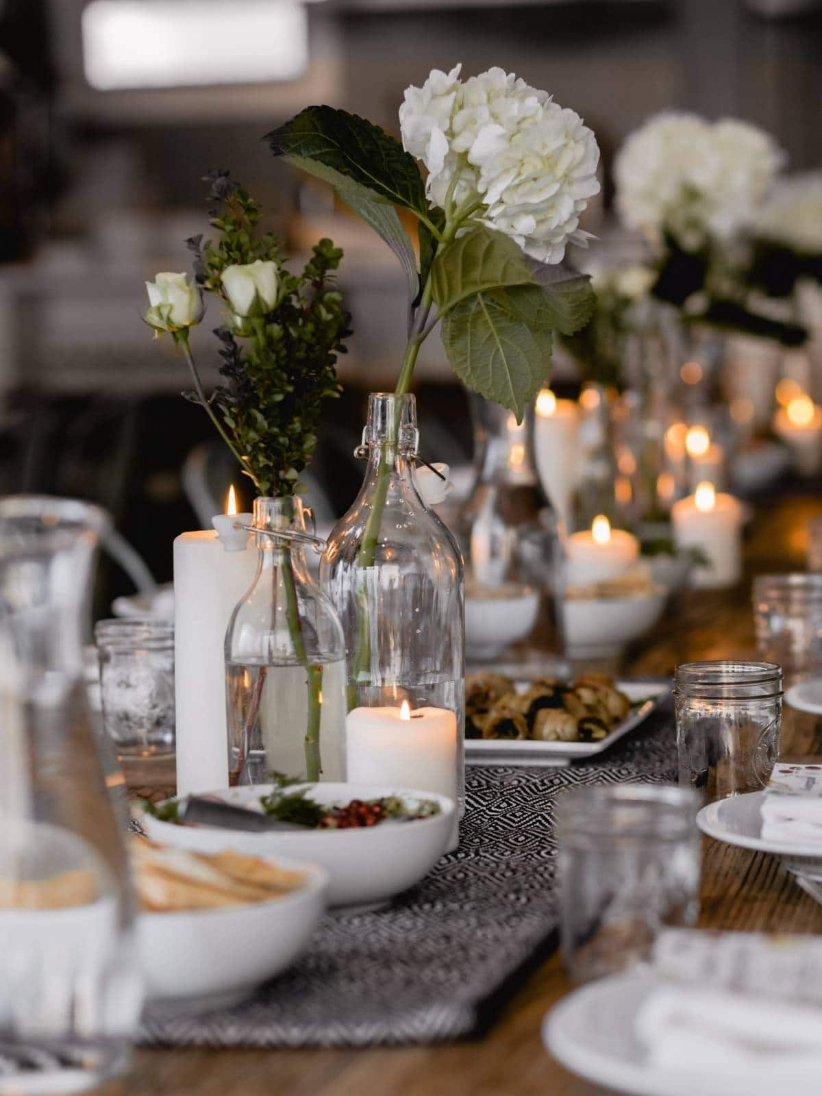 a table with white and green flowers down the middle