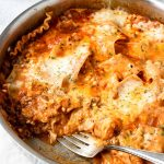 Close up of skillet lasagna with a piece taken out