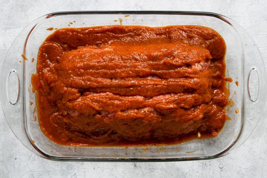 Marinara covering Italian meatloaf in a baking dish