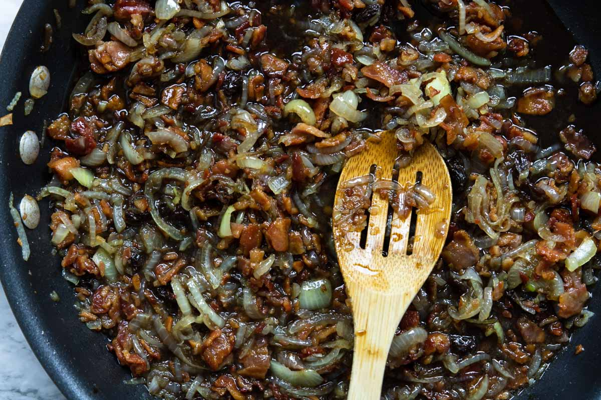 bacon jam cooking down in a skillet with a wooden spoon
