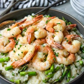 Instant Pot Shrimp Risotto in a grey bowl with a black and white napkin to the side