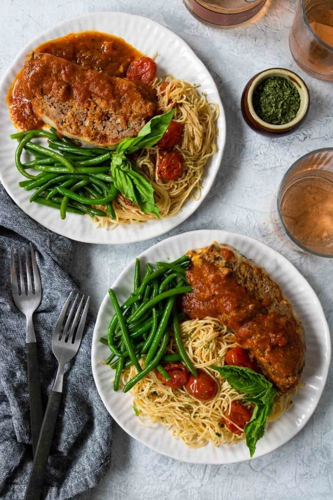 Italian Meatloaf dinner served on white plates with spaghettini and green beans