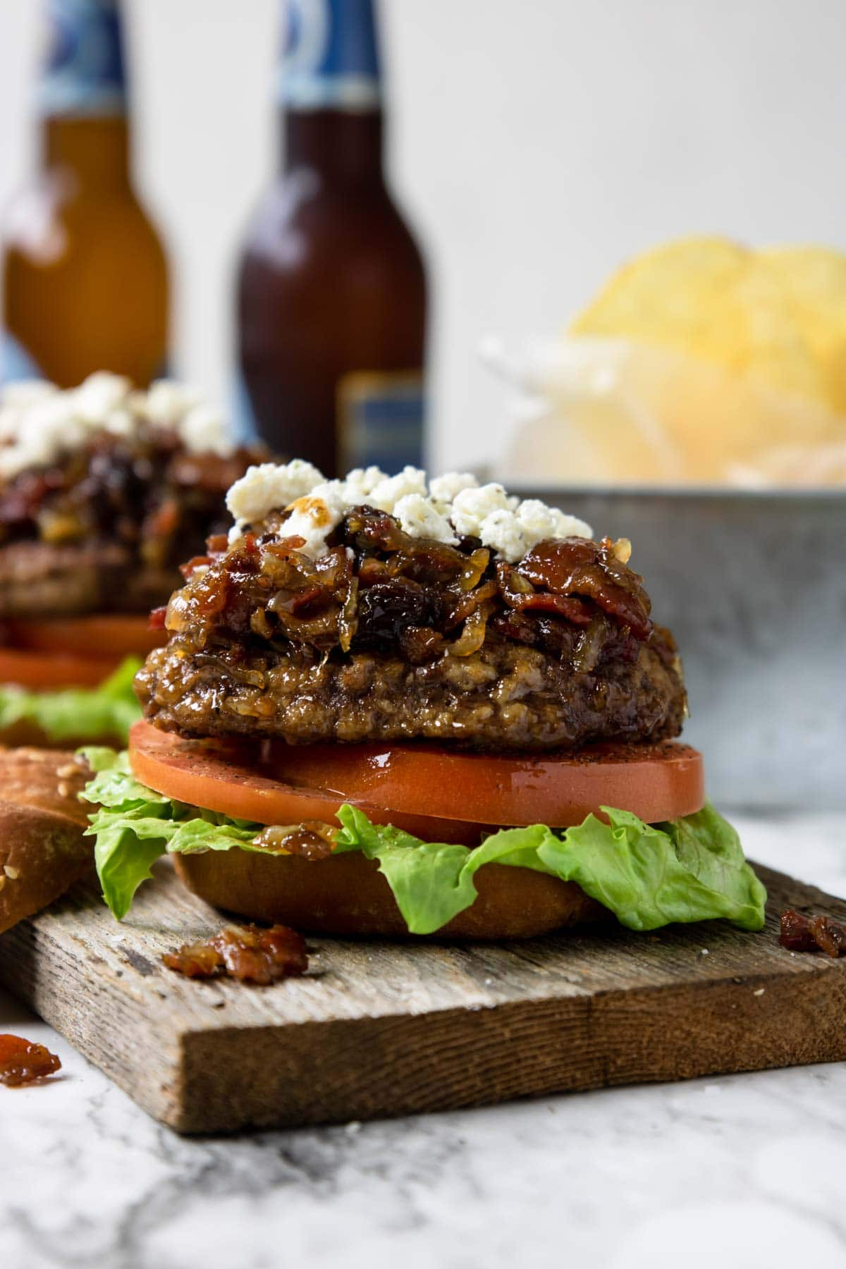 two burgers topped with bacon jam and boursin cheese and two bottles of beer in the background