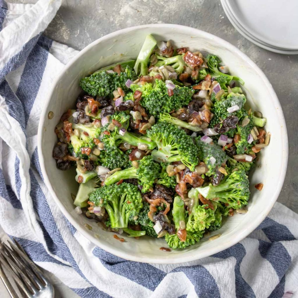 a large white bowl with a broccoli salad with bacon