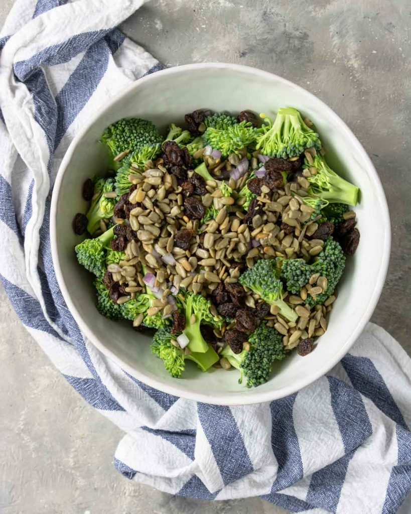 broccoli, onions, sunflower seeds and raisins in a bowl