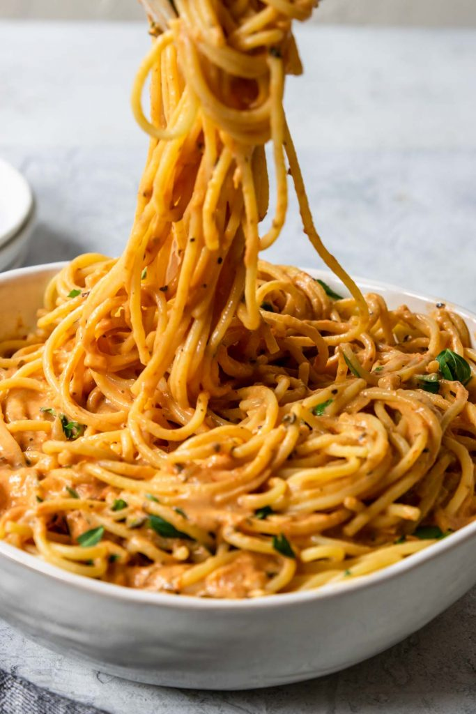 spaghetti being pulled from a bowl covered in tomato cream sauce