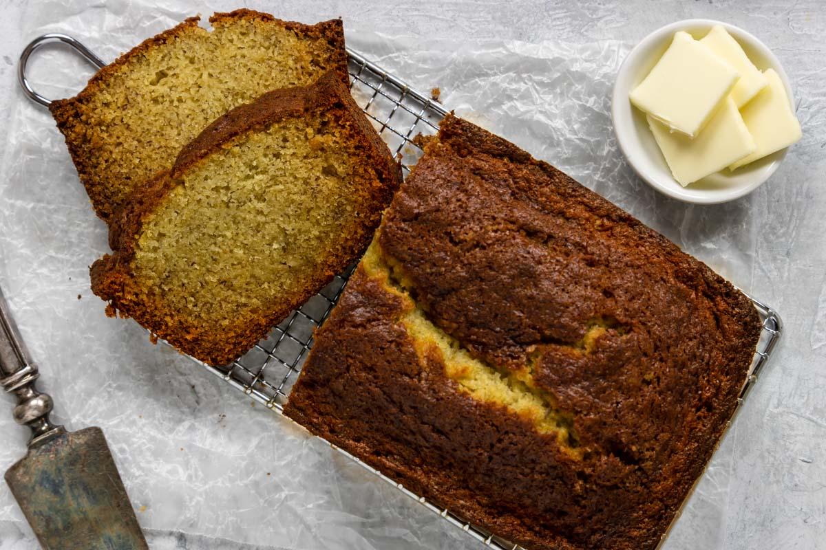banana bread sliced with butter to the side
