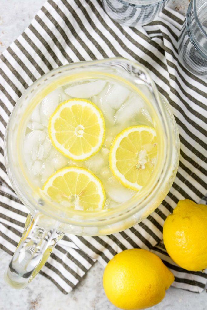 overhead photo of a pitcher of lemonade with 3 lemon wheels