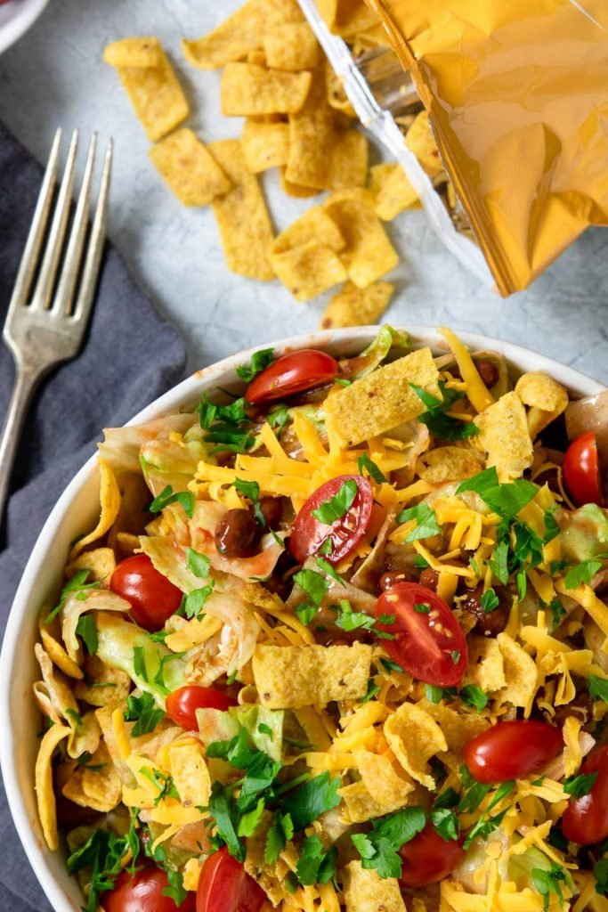 close up of vegetarian taco salad in a bowl topped with fritos