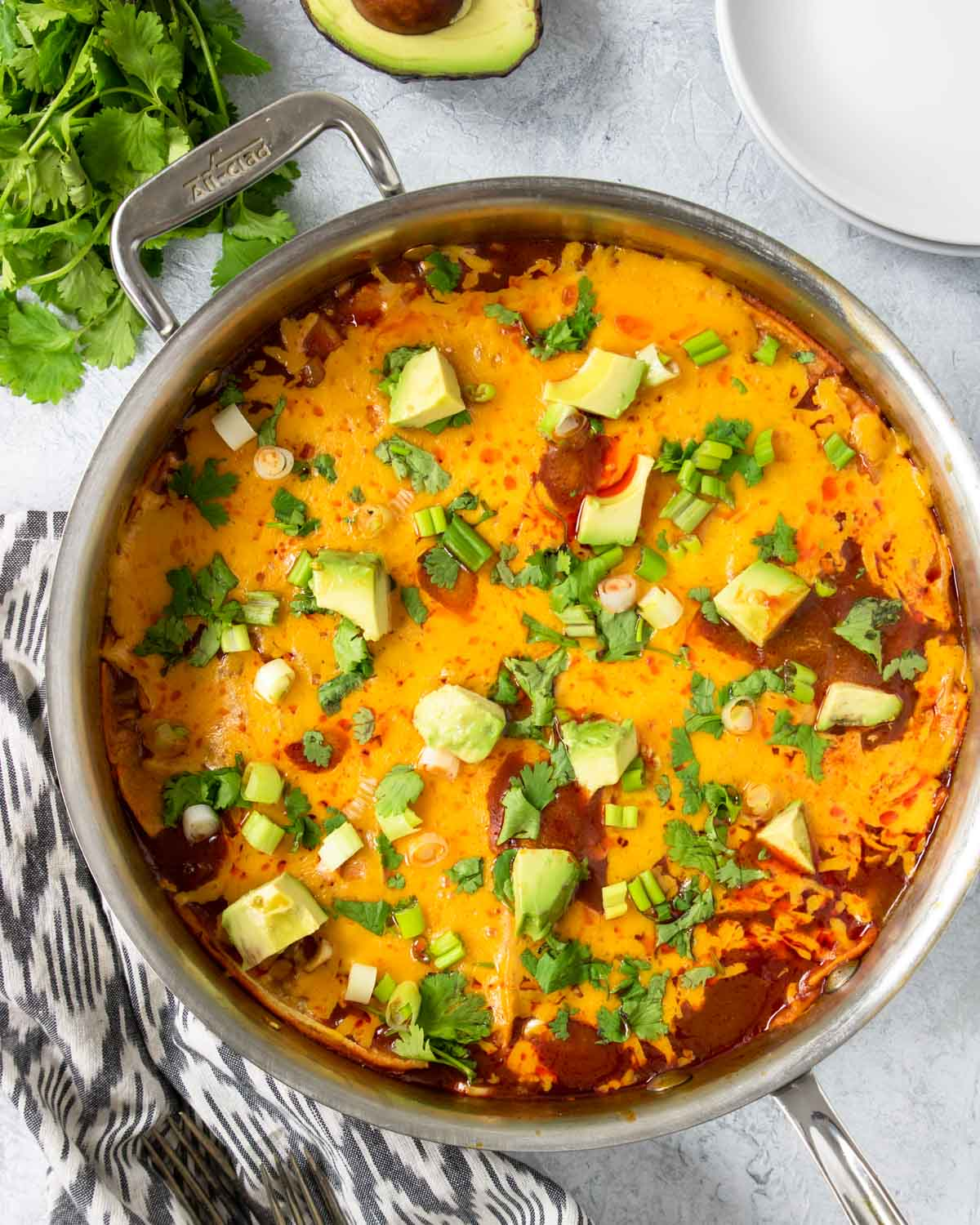 Skillet Enchiladas topped with cilantro, avocado, and green onions