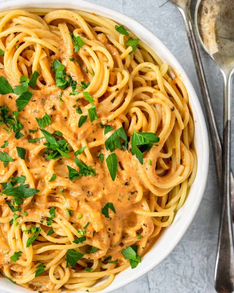 Spaghetti in a white bowl with creamy tomato sauce