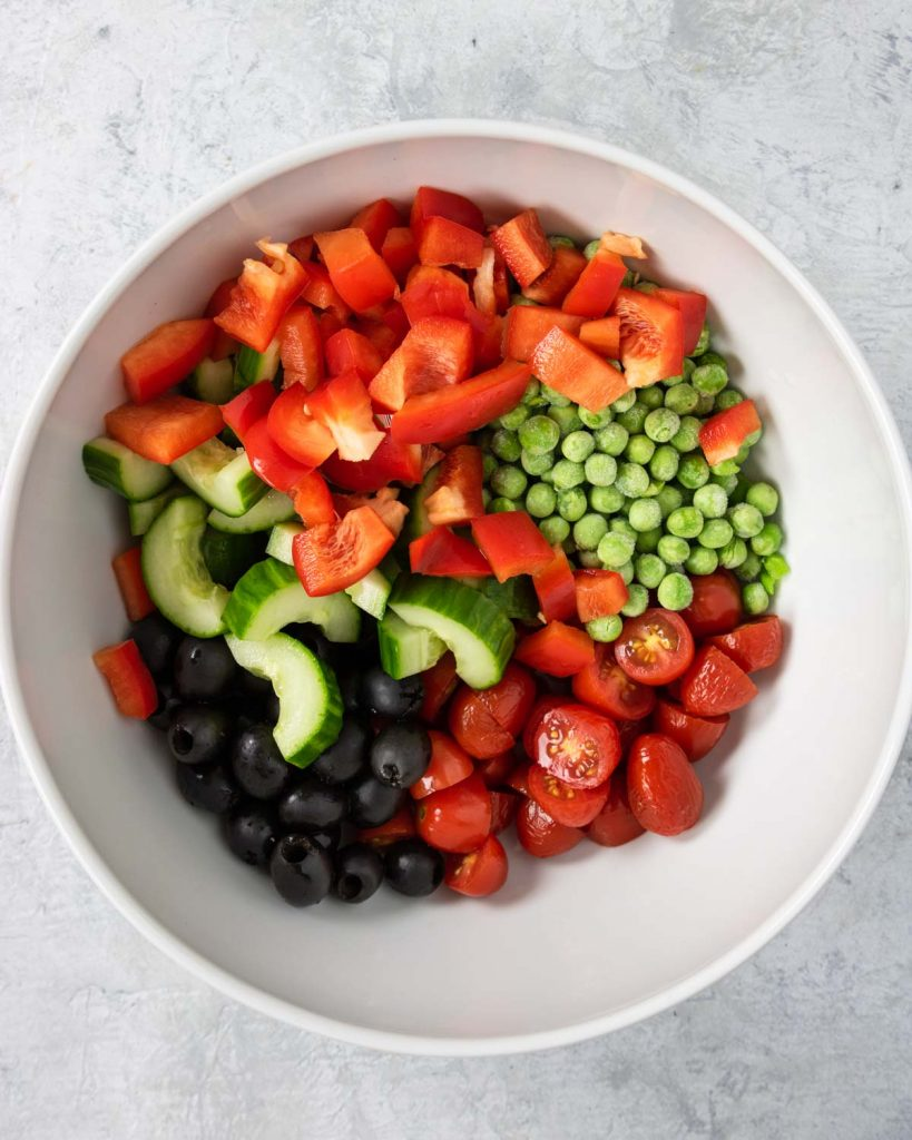 Black olives, peppers, tomatoes, cucumbers, and peas in a white bowl