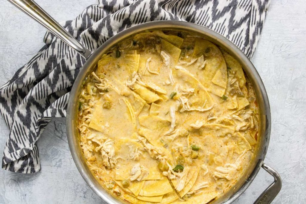 Skillet filled with light creamy sauce, chicken, and corn tortillas