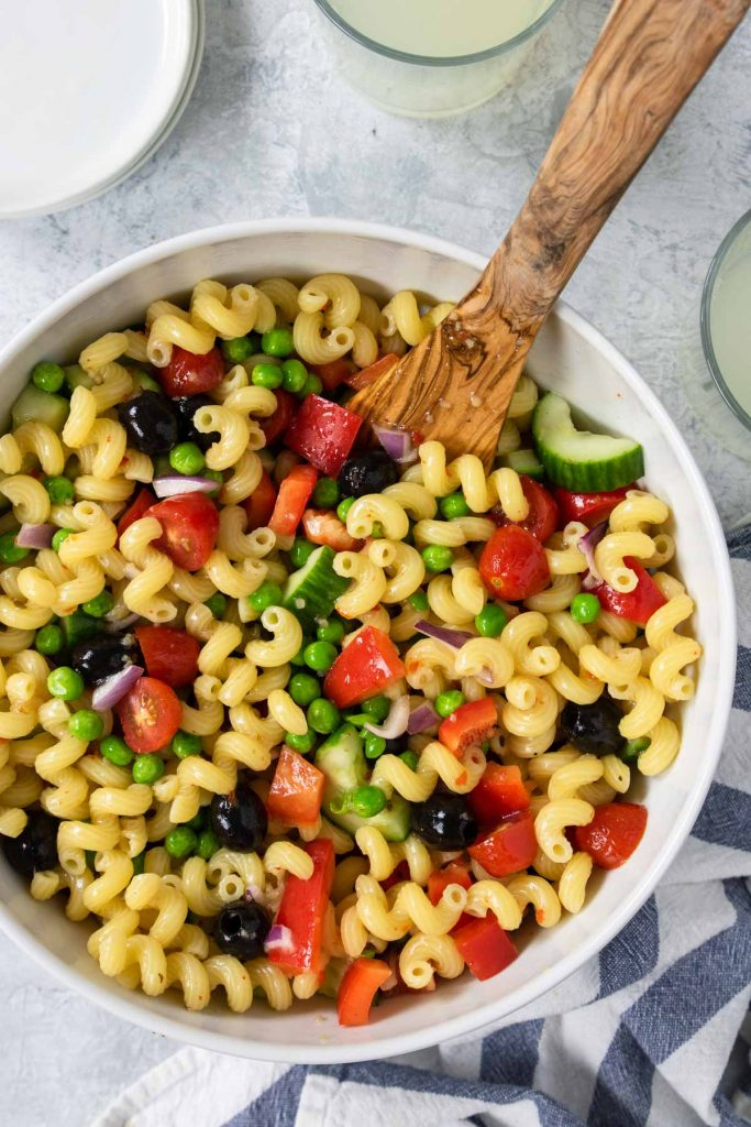 Veggie pasta salad in a white bowl with peas, black olives, tomatoes, and peppers