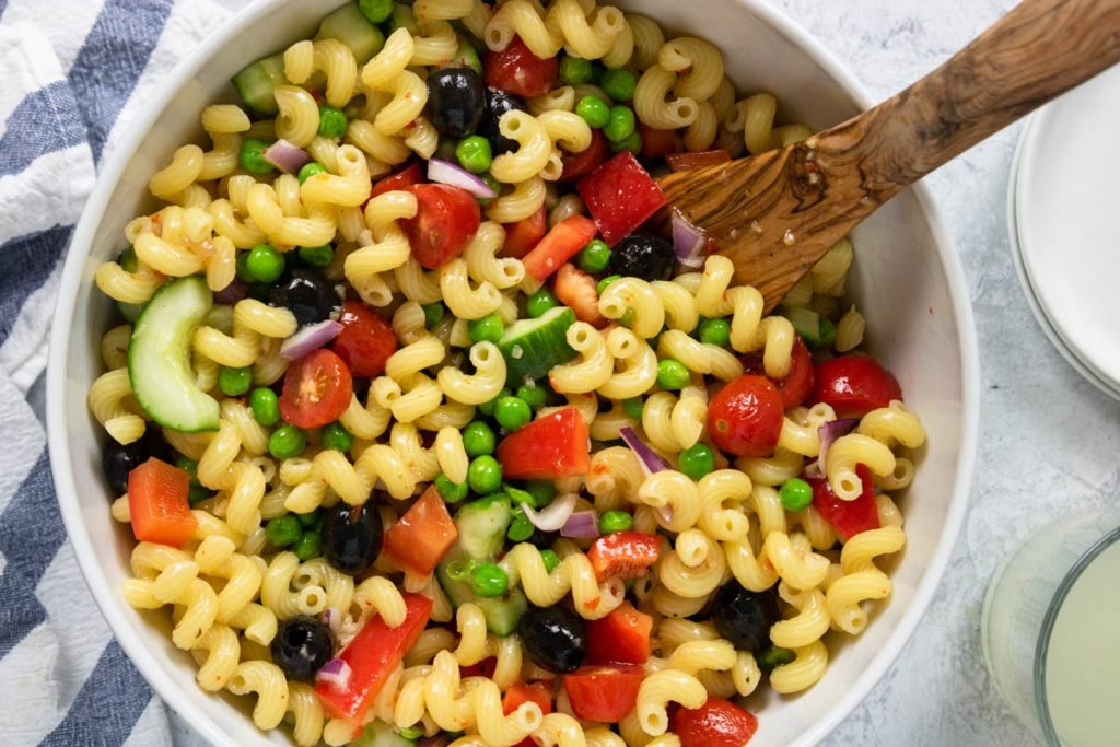 veggie pasta salad in a white bowl with cavatappi pasta and olives, peppers, tomatoes, cucumbers, and peas