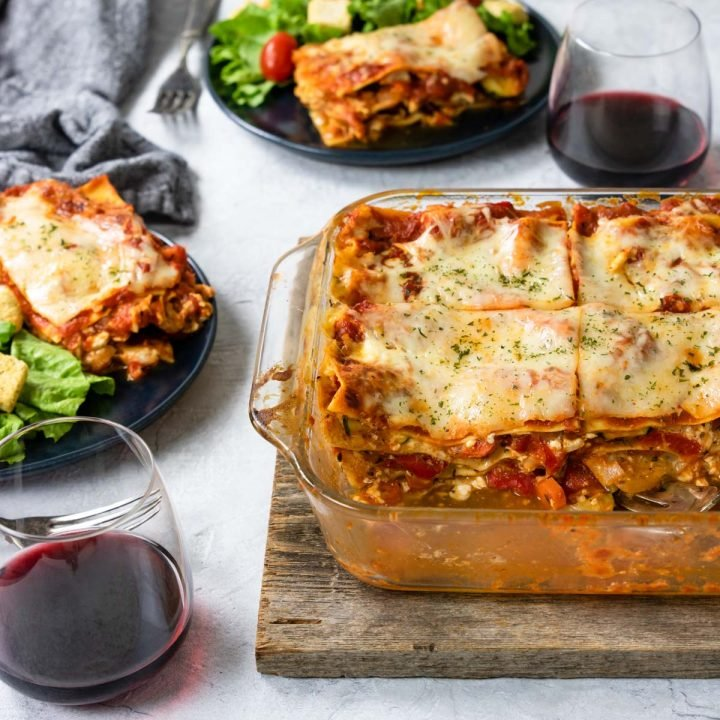 Table set with veggie lasagna in the center and two plates with lasagna and salad