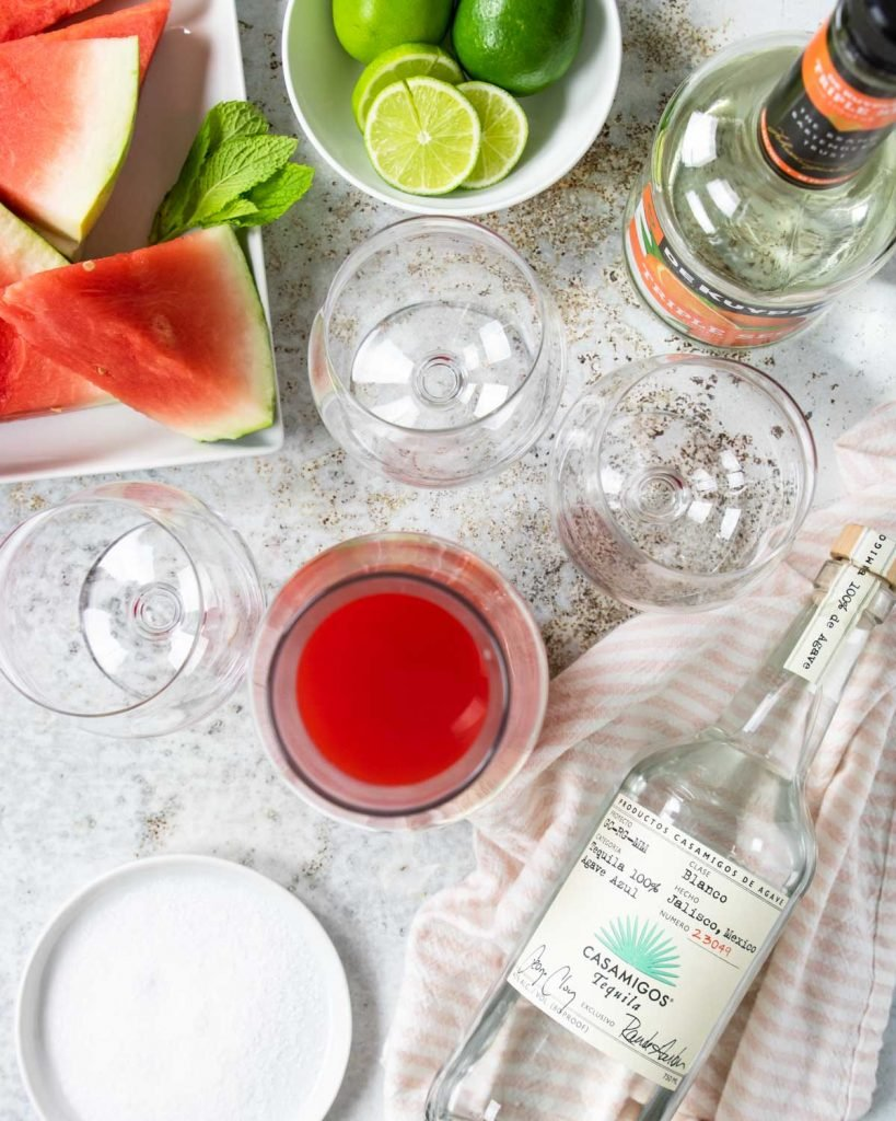all the ingredients to make watermelon margaritas; tequila, triple sec, watermelon juice and limes