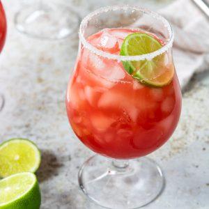 a watermelon margarita in a stemmed glass with a sugar-salt rim and a lime garnish