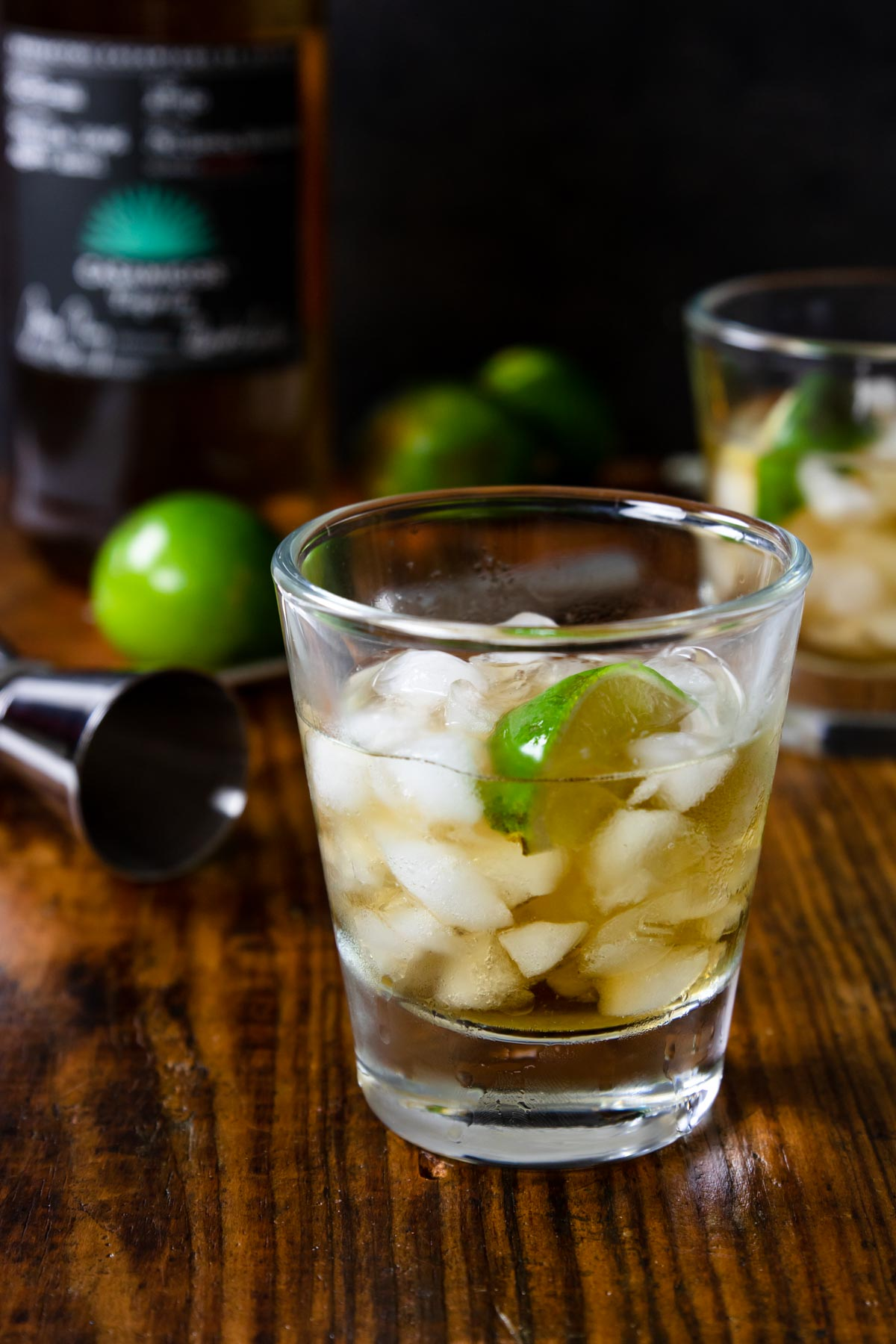anejo tequila on the rocks in a glass with a lime and a bottle of tequila in the background