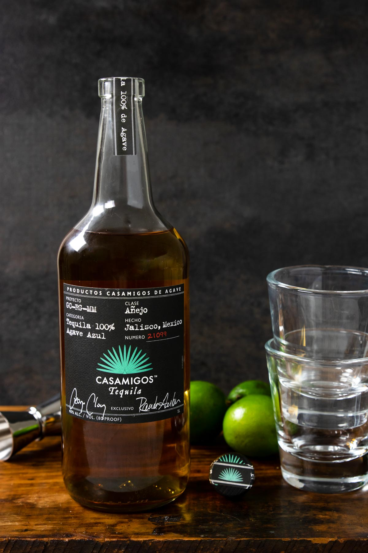 a bottle of casamigos anejo tequila, two glasses stacked, limes and a shot jigger