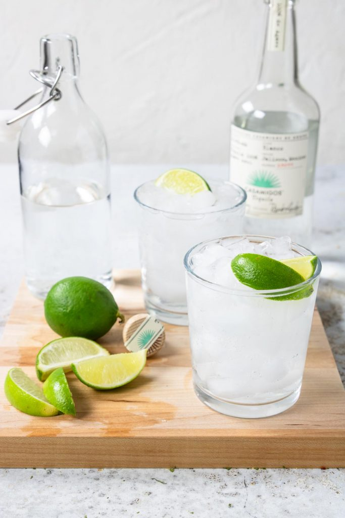 a cutting board with two cocktails, limes and a bottole of seltzer water. Also a bottle of Casamigos tequila in the background