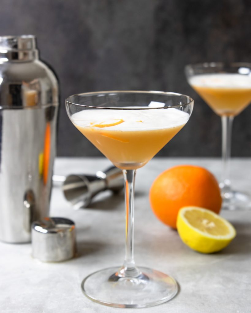 A tequila sour in a coupe glass with orange and lemon in the background
