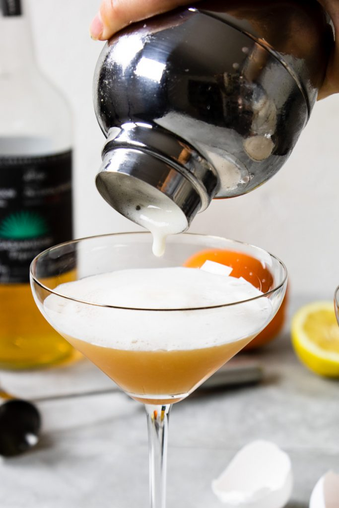 Pouring a frothy cocktail from a shaker into a coupe glass