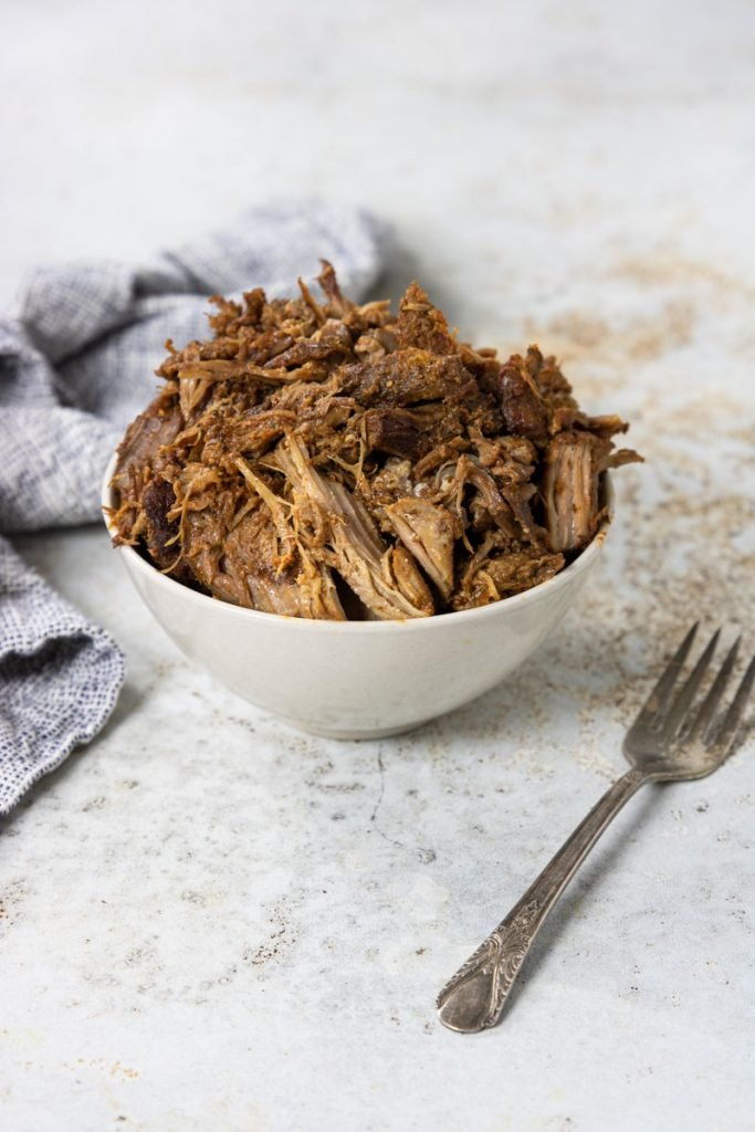 a white bowl of whole30 pulled pork with a fork to the side