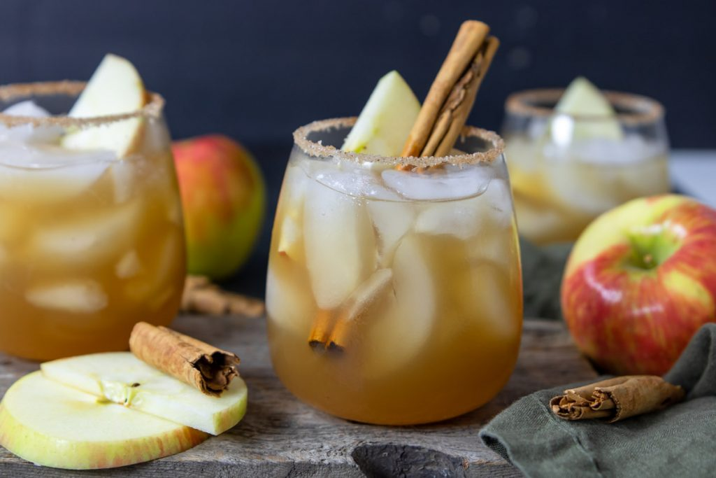 Apple Cider Margaritas in a glass with cinnamon sticks and apples