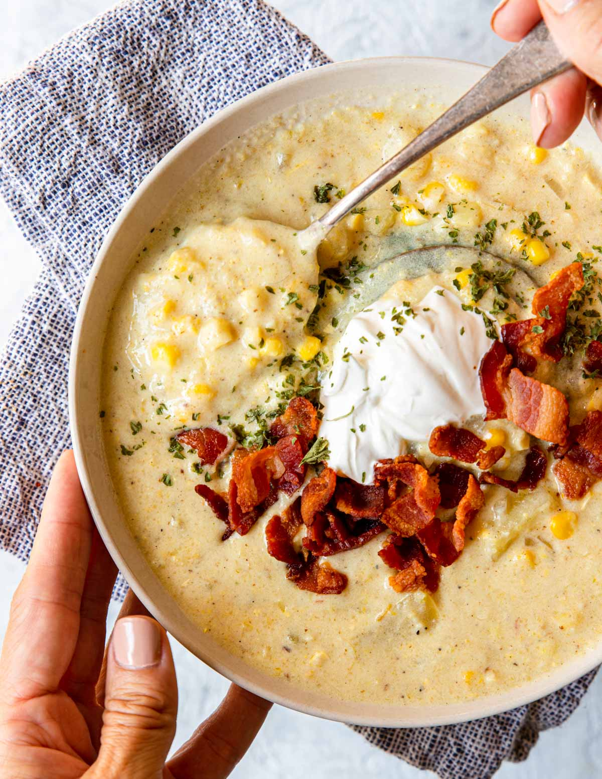 eating a bowl of chowder with a spoon, topped with sour cream and bacon
