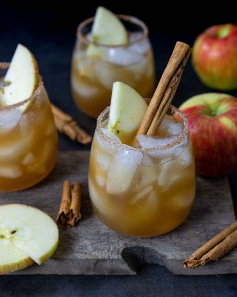 a table with apple cider margaritas with cinnamon sugar rims and apple cinnamon stick garnish