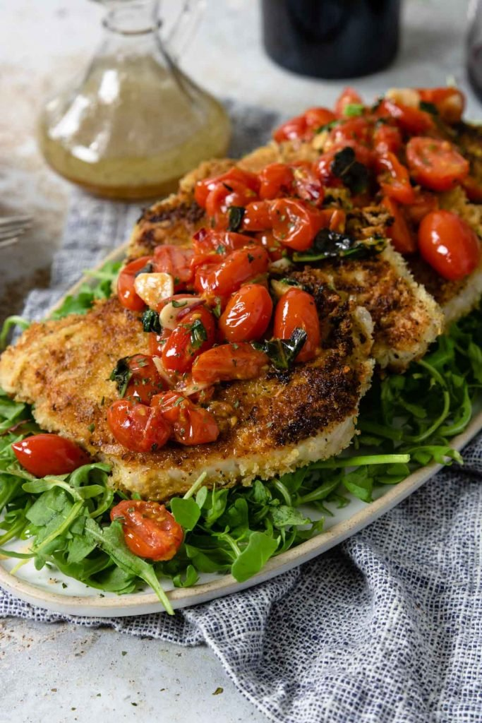 pork milanese on a platter topped with tomatoes and garlic