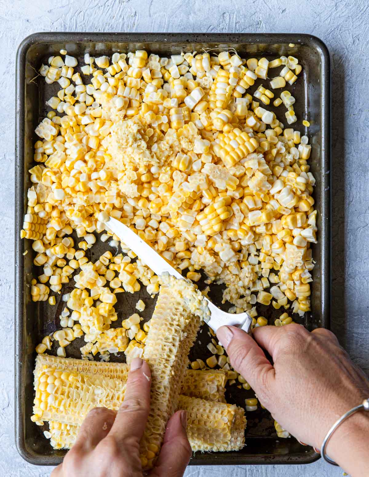 Removing corn from the cob and scraping the pulp and milk