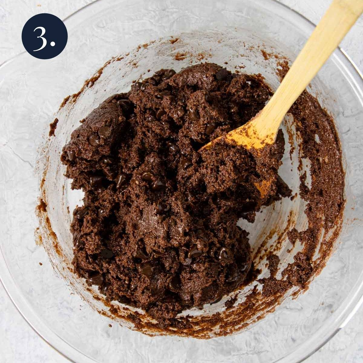 brownie batter in a bowl with a wooden spoon