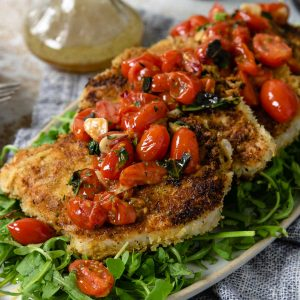 pork milanese topped with a tomato relish