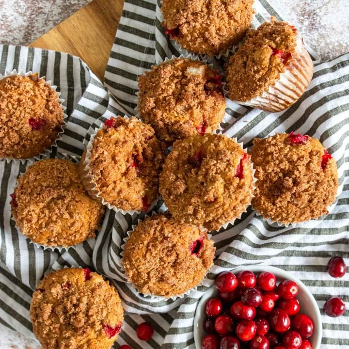 cranberry orange muffins topped with a cinnamon crumble, on a black and white napkin, fresh cranberries to the side