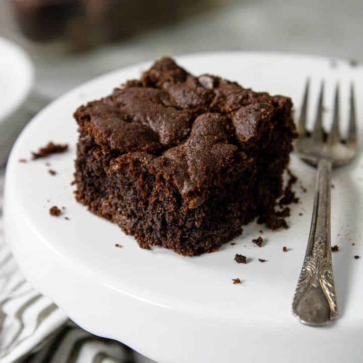 one brownie on a cake plate with crumbs around and a fork