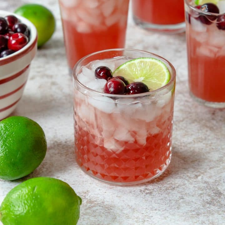 cranberry punch in a glass with cranberries and limes