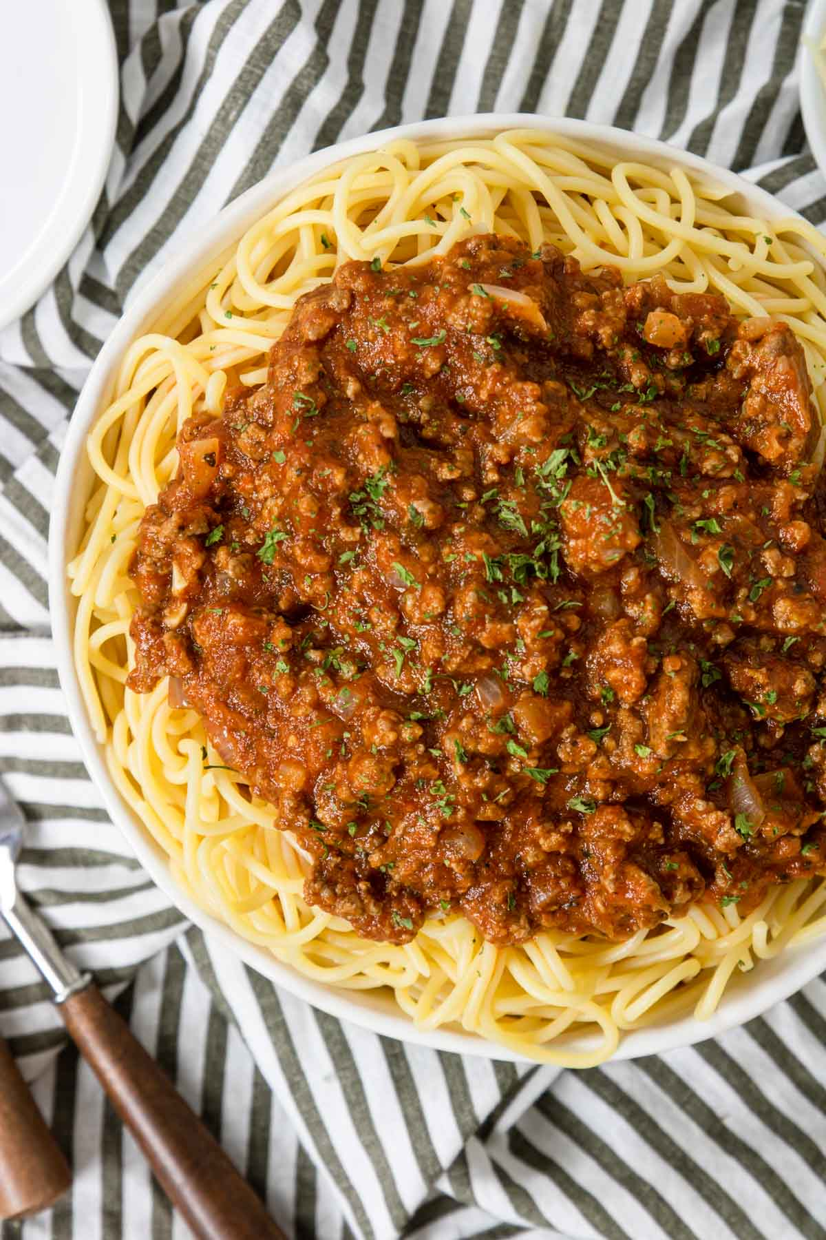 spaghetti with meat sauce on top and garnished with parsley