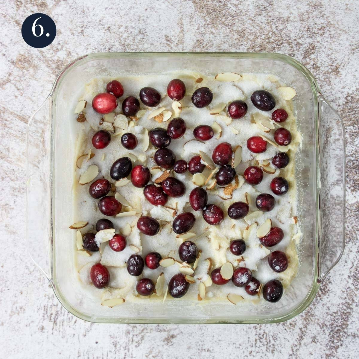 cake batter in an 8x8 with cranberries, almonds and sugar on top