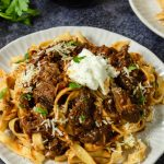 tagliatelle pasta topped with beef ragu and a dollop of ricotta cheese