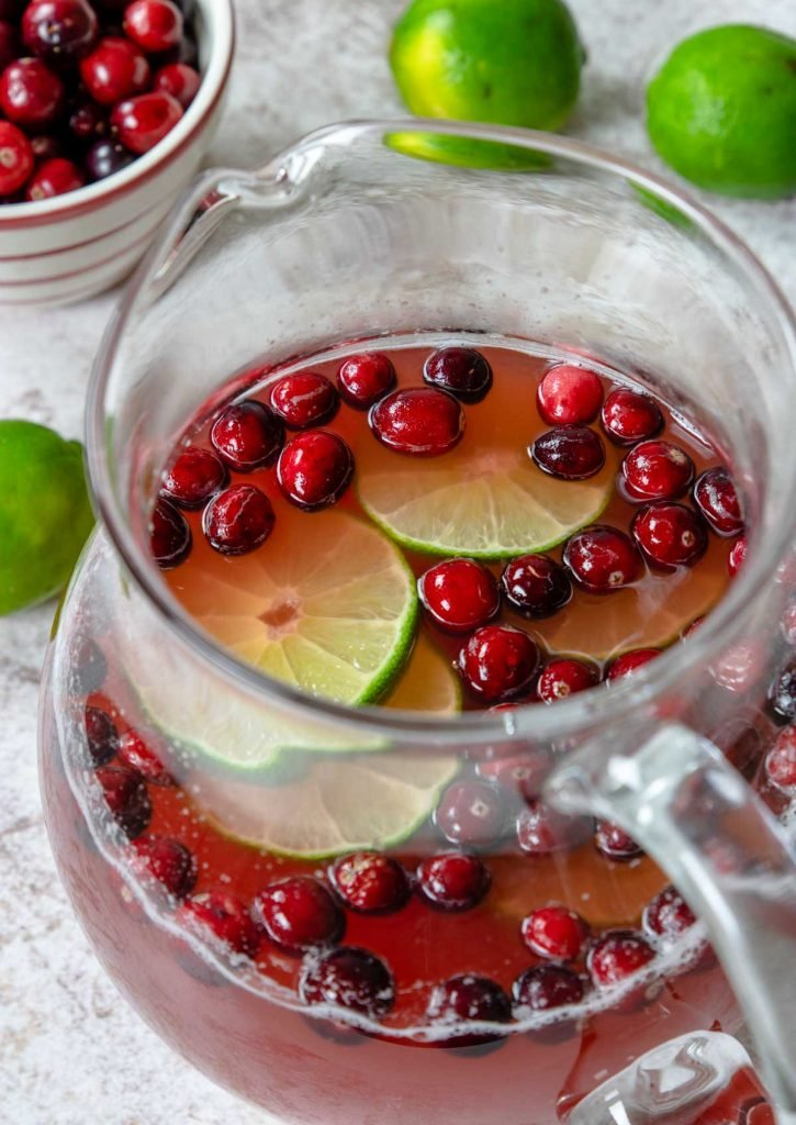 a pitcher of cranberry punch garnished with cranberries and limes