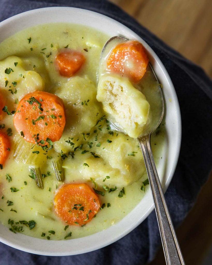 Chicken and dumplings in a bowl with a dumpling cut open