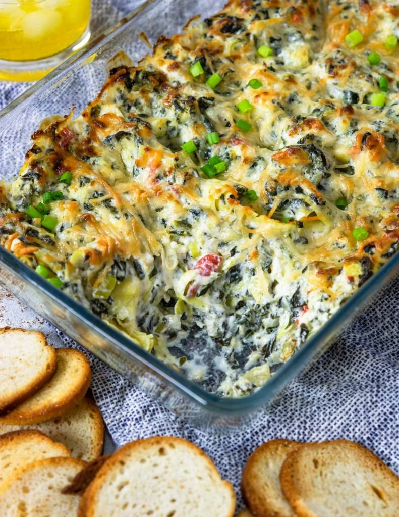 Spinach artichoke dip in a baking dish with bagel chips for dipping