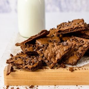 a pile of brownie brittle pieces and a glass of milk